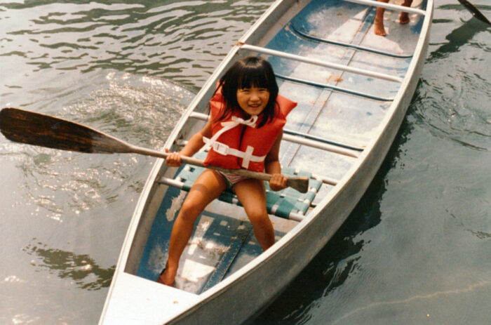 A young Asian girl wears an orange life preserver and sits in a canoe while holding a paddle
